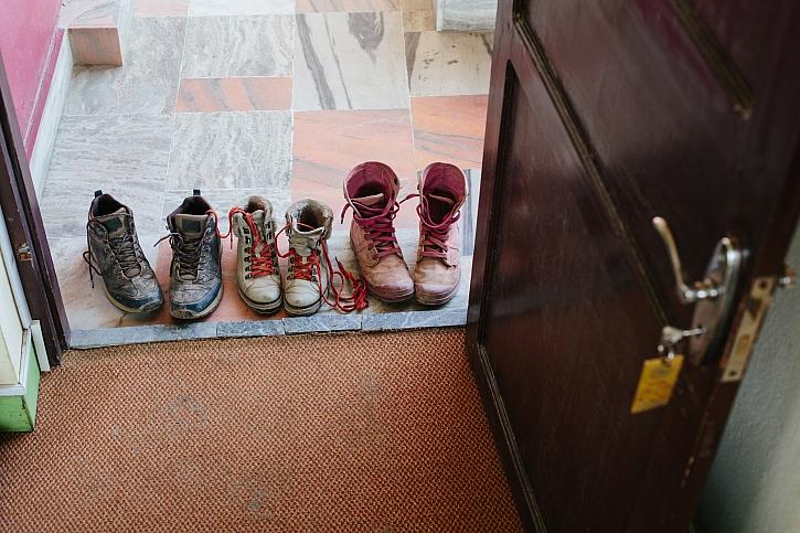 Špinavé zablácené boty na prahu u dveří a koberec