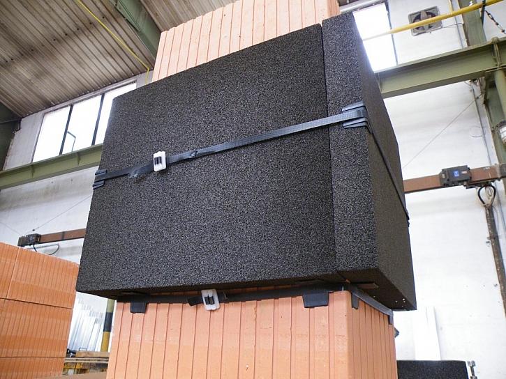 Všechny čtyři slepené desky okolo komína stáhneme dodanou stahovací páskou. Před konečným stažením na hrany desek umístíme další plastové rohy, aby desky chránily před poškozením.