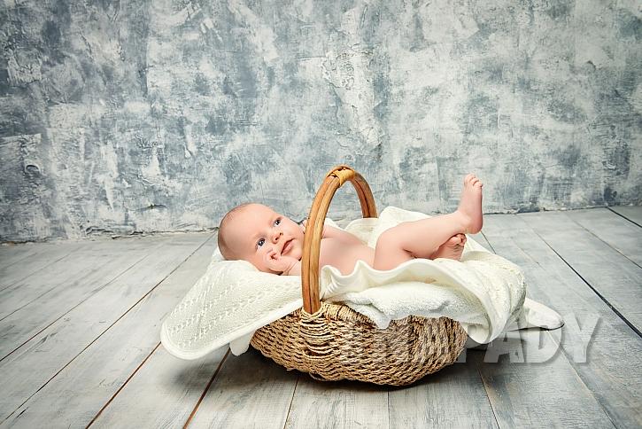 Malé dítě v košíku na dřevěné podlaze