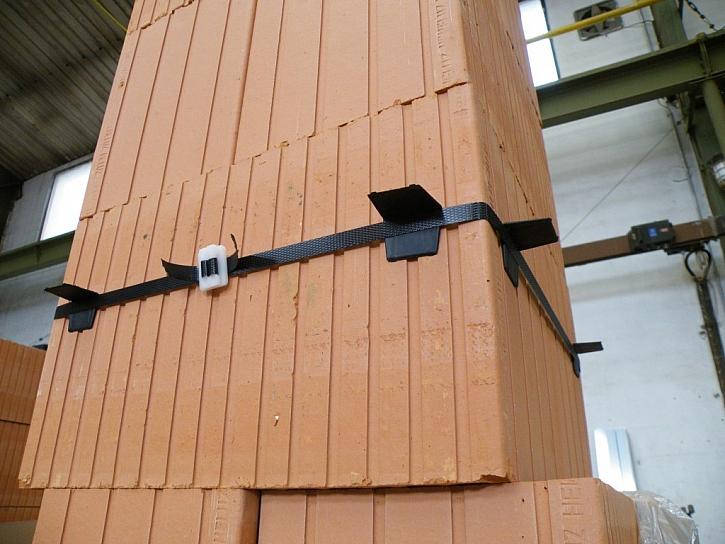 Do místa spodní části prostupu připevníme okolo komína pomocí plastových sponek montážní pásku. Za ni zavlékneme plastové rohy, které budou prostup držet po dobu zaschnutí tmelu.