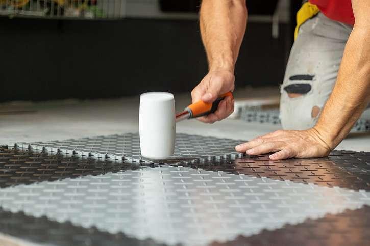 Dílce gumové podlahy je potřeba do sebe zatlouct gumovou palicí