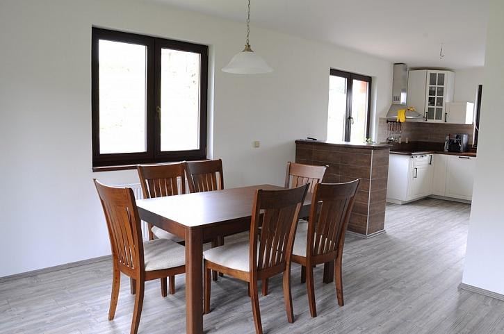 Jídelní stůl se židlemi v obývacím prostoru ladí s kuchyňskou deskou