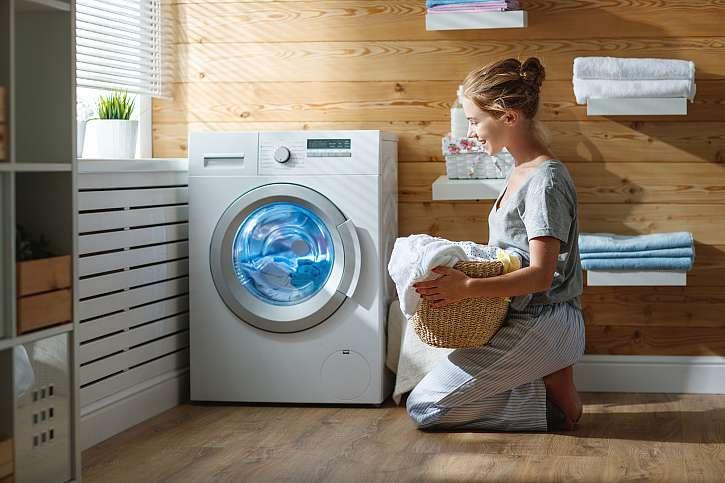 Žena klečící u pračky s košem prádla
