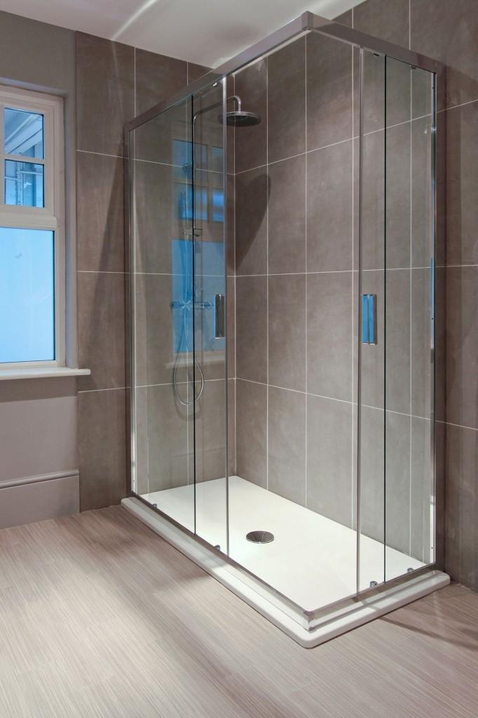 Luxusní prostorný sprchový kout s nízkou, profilovanou vaničkou a skleněnými posuvnými dveřmi zve k použití