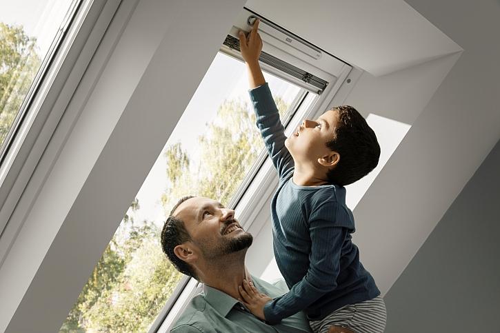 Chlapec v náručí muže u okna