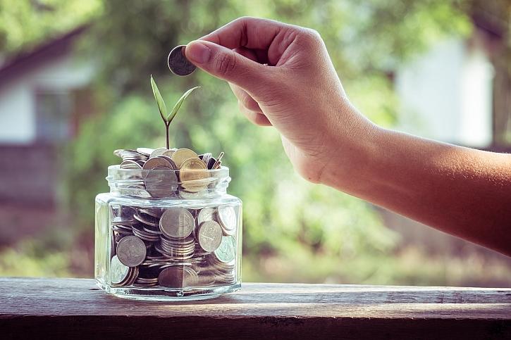 Ruka hází mince do skleněné nádoby