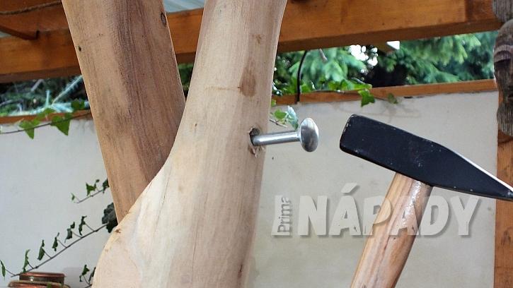 Jak vyrobit stojan na šaty z větví: do předvrtaného otvoru doklepneme šrouby kladívkem