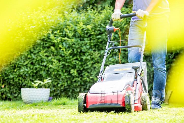 Muž sekající trávu sekačkou