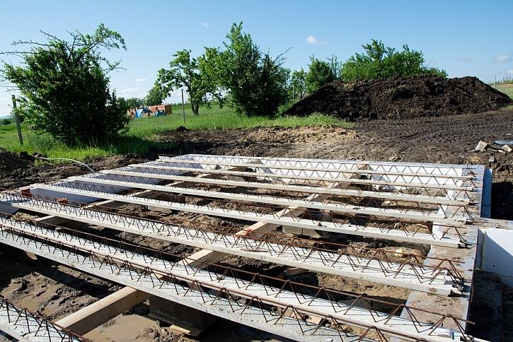 Na půdorys nadezdívky se položí izolační podložka z tvrzeného polystyrenu a na ni se ukládají železobetonové nosníky