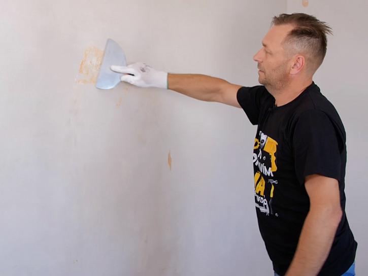 Minutový manžel škrábe staré nátěry ze zdi a připravuje tak byt na vymalování.