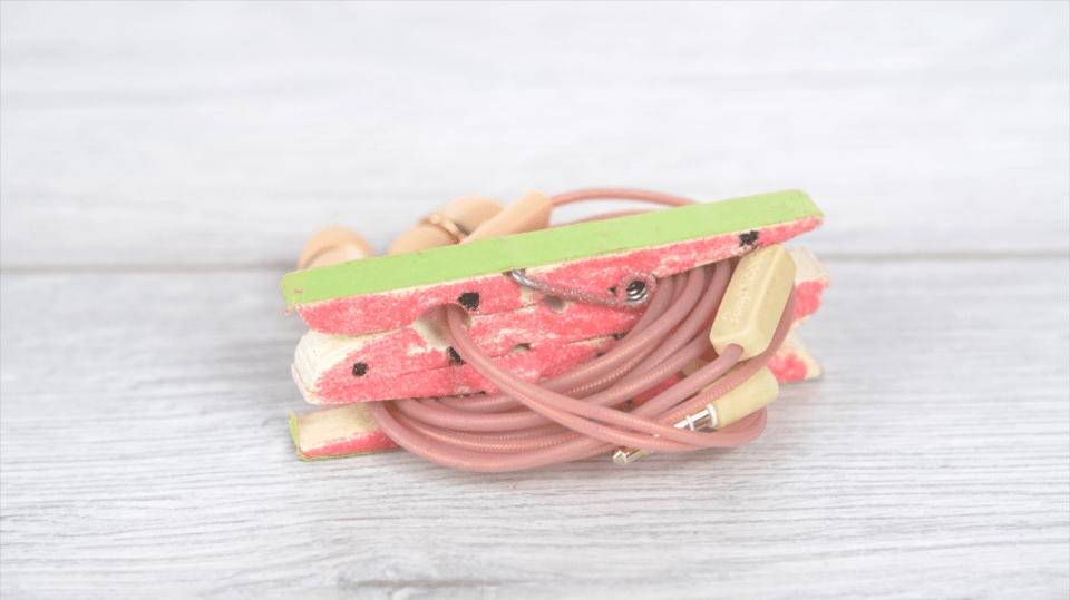 Držák z kolíčků na prádlo vyřeší problém se zamotanými sluchátky: Sluchátka vkousku melounu