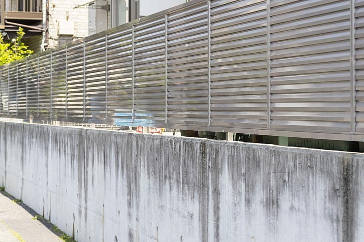 Betonový plot s kovovým vrškem je fádní a nehezká záležitost