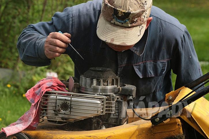 Muž opravující motor sekačky