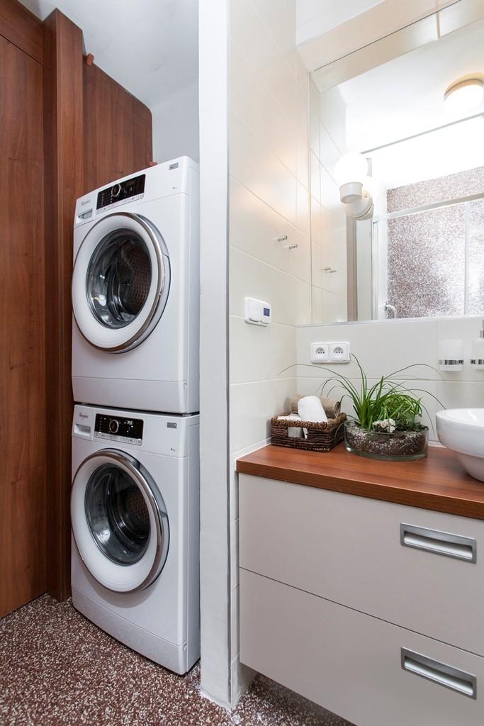 Moderní pračka a sušička zůstaly za dveřmi, pod umyvadlem jsou prostorné zásuvky