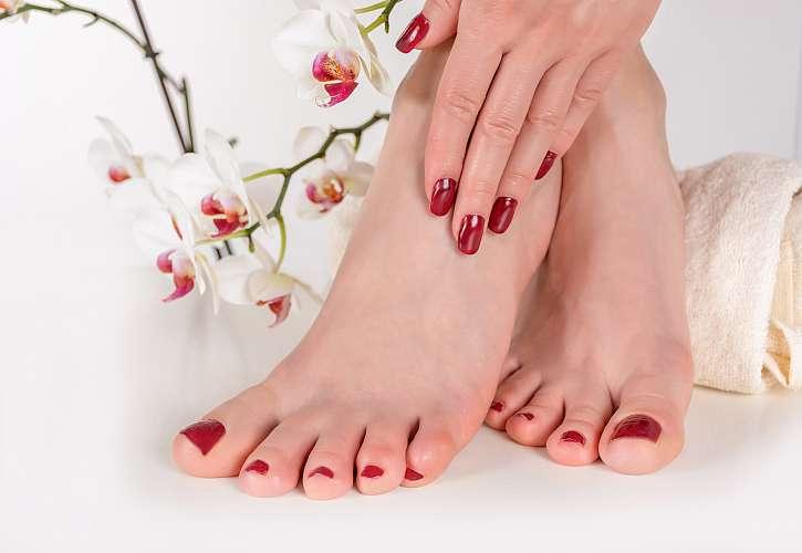 Krásné nohy a ruce se stejně červeným lakem s orchidejí v pozadí