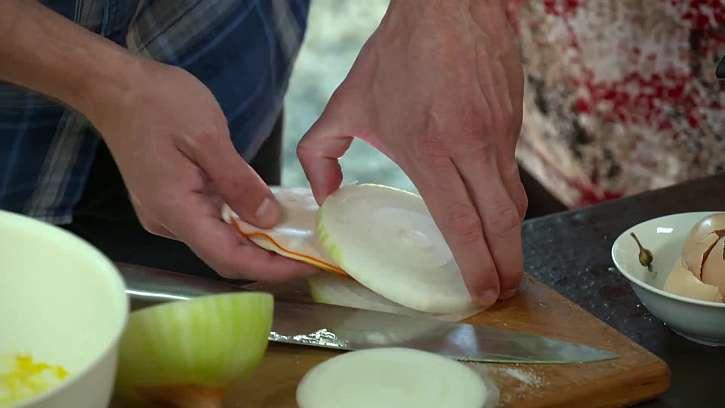 Prokládání cibulových koleček šunkou a sýrem.