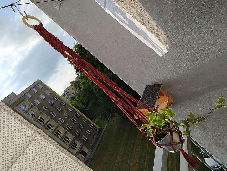 Macramé držák na květinu zavěšený na balkoně