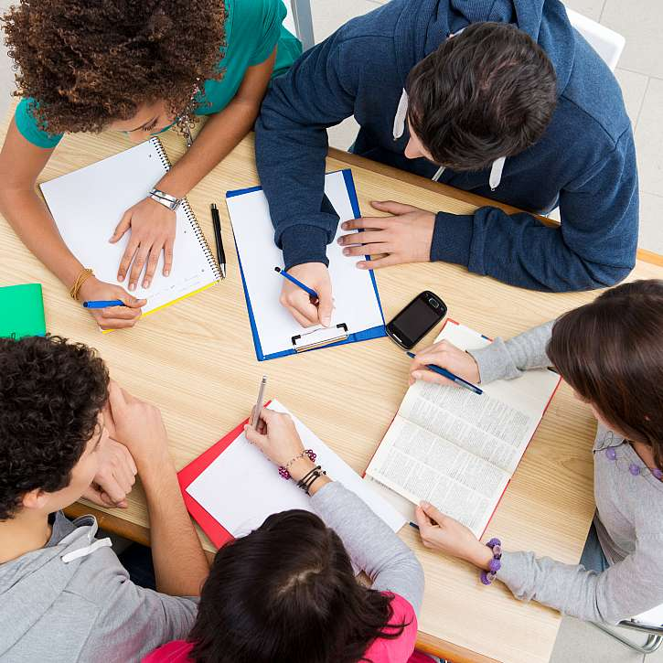 Žáci píší u stolu