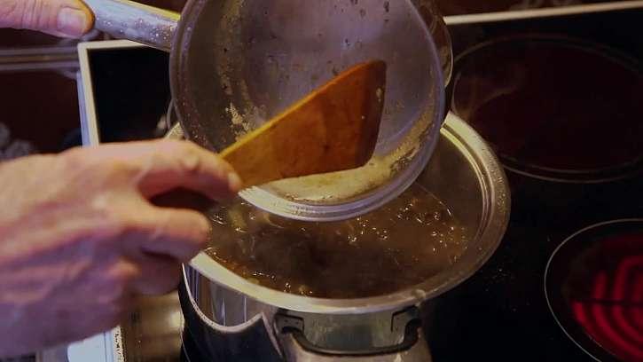 Přelévání másla do hrnce s polévkou