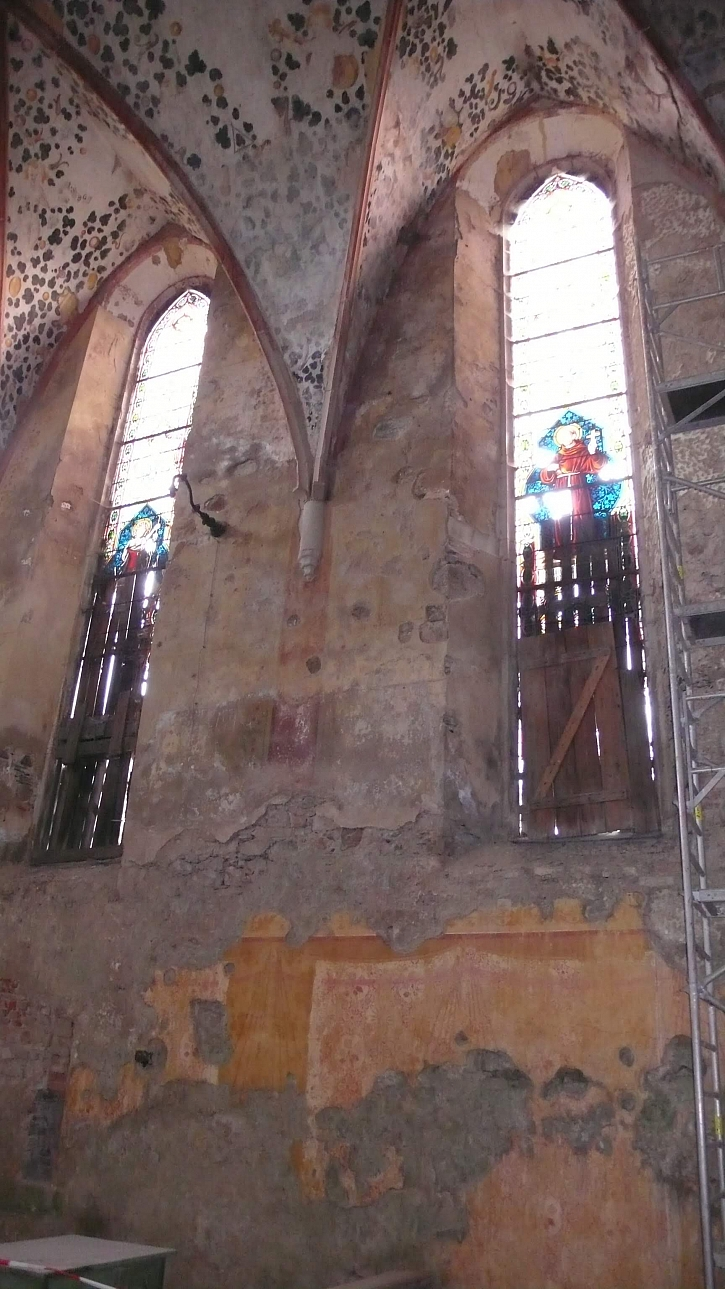 vitráže v katastrofálním stavu, zabedněné prkny