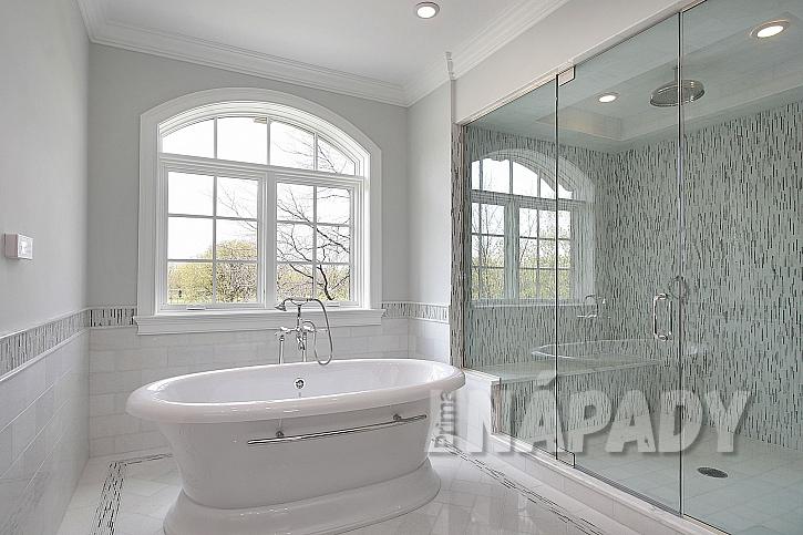 Koupelna v bílé barvě s velkým sprchovým koutem a volně stojící vanou