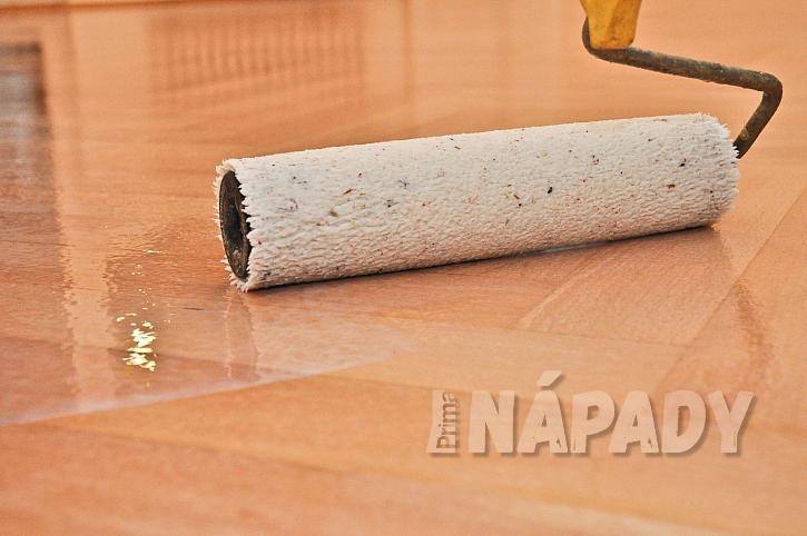 Nanášení laku válečkem na dřevěnou podlahu