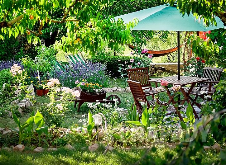 Slunečník u stolu dotváří pohodu uprostřed zahrady (Zdroj: depositphotos.com)