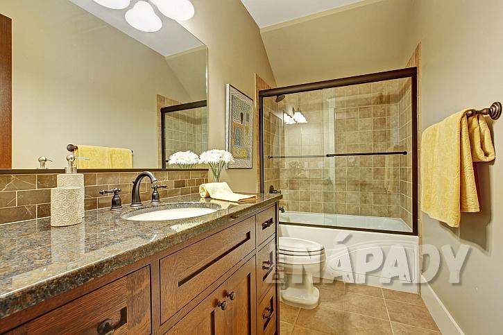 Interiér koupelny s vanou se skleněnou zástěnou