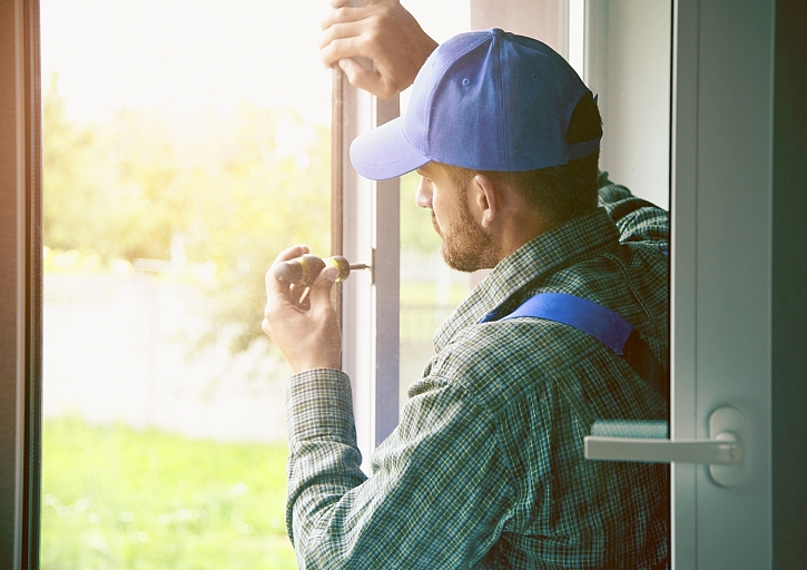 Servisní muž instaluje okno se šroubovákem