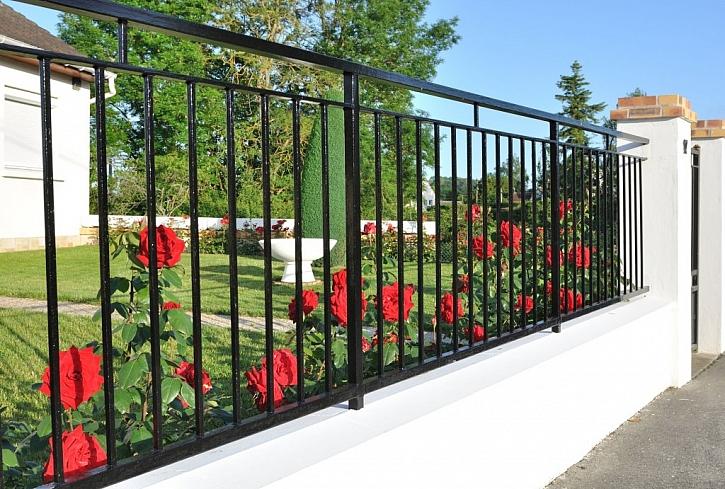 Kombinace plné podezdívky a sloupků s kovovým plotem působí čistě a bytelně