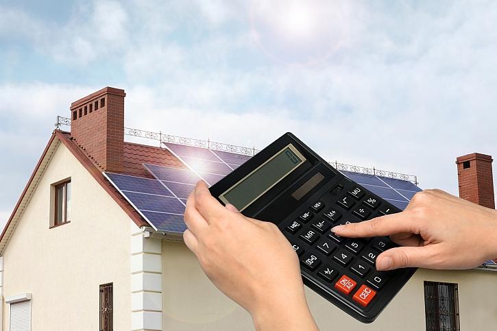 Ruka s kalkulačkou, v pozadí dům s fotovoltaikou