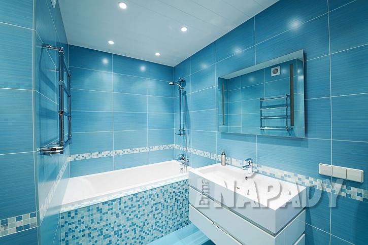 Modrá koupelna malých rozměrů s bezrámovým zrcadlem