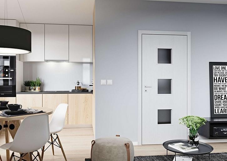 Dub Arktický Bílý na interiérových dveřích Domino od SAPELI. Tento vzhled dveří se čtvercovými okénky uvítají všichni, co mají rádi symetrii a řád