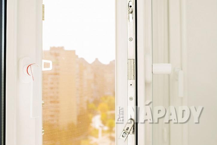 Otevřené okno s výhledem na slunnou ulici