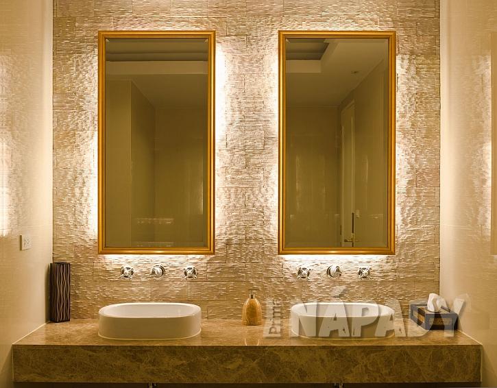 Zrcadla ve zlatém rámu v koupelně se dvěma umyvadly