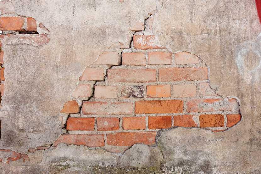 Vlhkost z půdy viditelně poškozuje zdivo domu, omítka časem úplně opadá