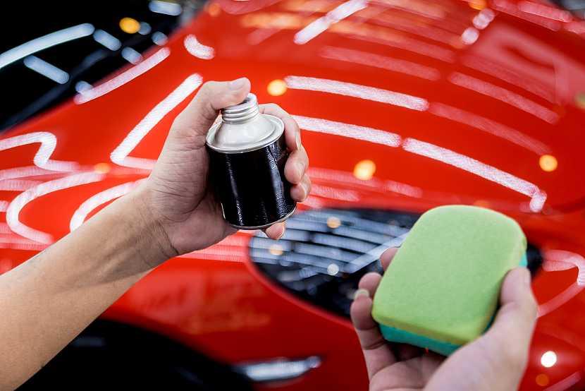 Vosk na auto s houbičkou před autem