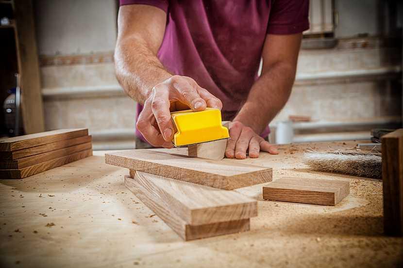 Muž brousící dřevo
