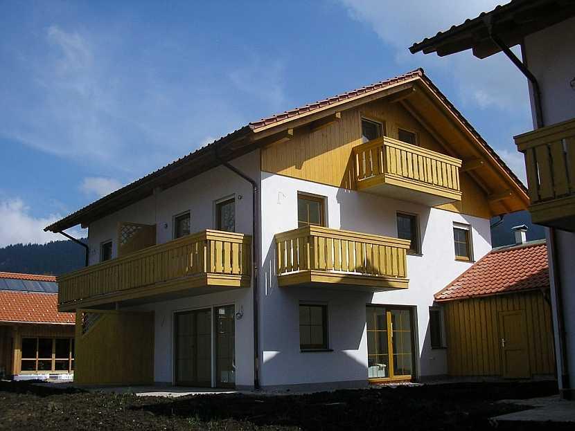 Balkony na domě ladí i s obložením štítu, dělicí stěnou, s typem oken a garážovým přístavkem