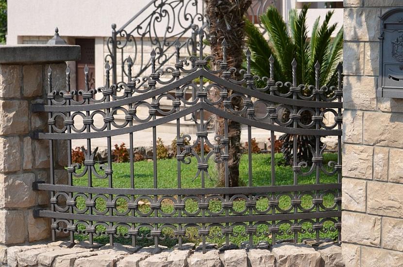 Kovaný plot se sloupky z umělého betonu je vysoce estetické řešení
