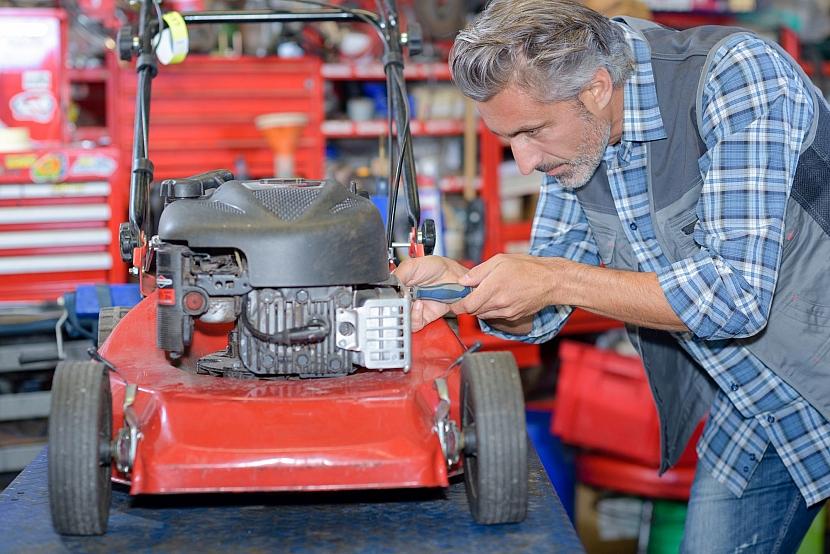 Údržba zahradního stroje - muž kontroluje stav sekačky