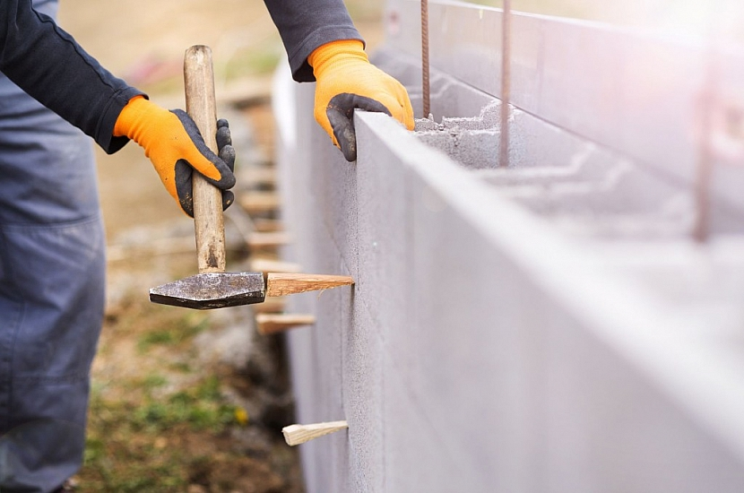 Dělník na stavbě staví plot ze ztraceného bednění