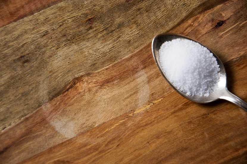 Vodní skvrna na dřevě se lžící soli