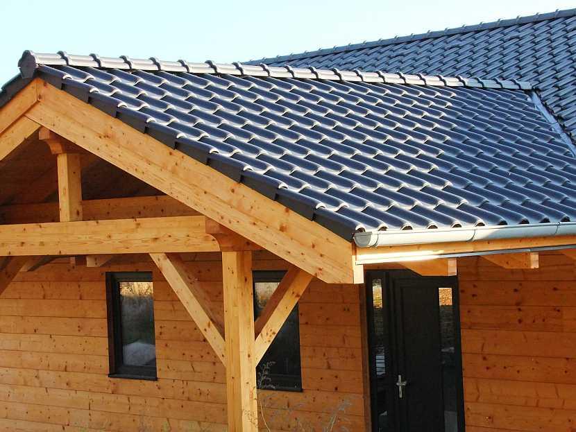 Dřevostavba má zastřešení vchodu řešené jako součást celého domu