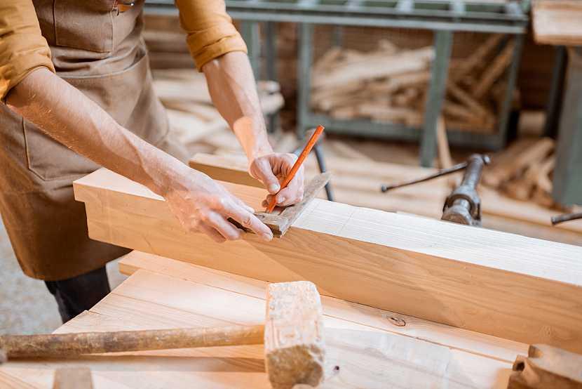 Muž vyznačující na dřevo body, kde bude řezat