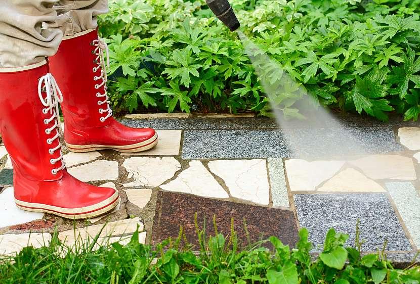 Čištění chodníku v červených gumácích tlakovým čističem