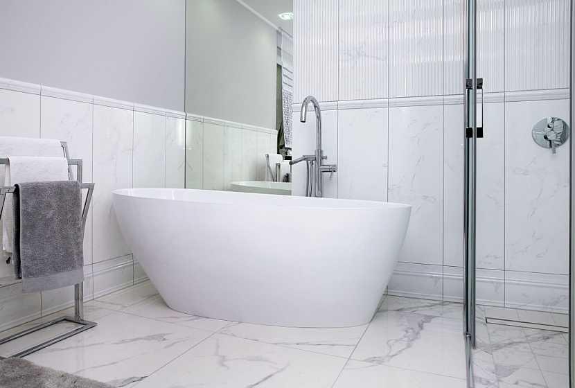 Leštěné kamenné dlaždice na podlaze dodají koupelně luxusní vzhled
