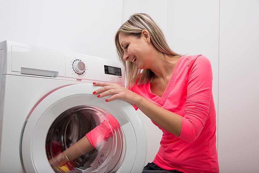 Žena sedící u pračky, která kontroluje její obsah
