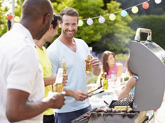 Volný čas, jídlo, lidé a svátků precizní. Muž vaření masa na grilu na oběd v zahradě (Zdroj: Depositphotos)