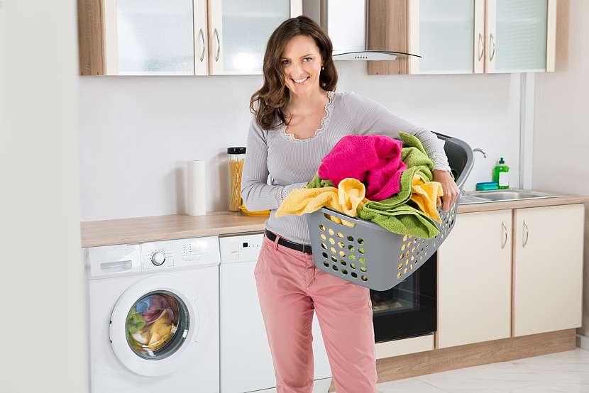 Žena v kuchyni u pračky s plným košem barevného prádla